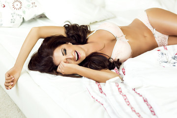 Smiling brunette lady in bed