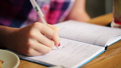 Teenage girl hands writing in notebook, doing homework