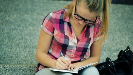 Teenager writing in notebook, sitting on stairs at school