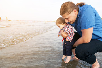 Young father holding his child over sea water having fun