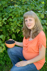 The pregnant woman with a bowl of black currant in a garden