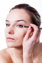 Woman making make-up using eyeliner