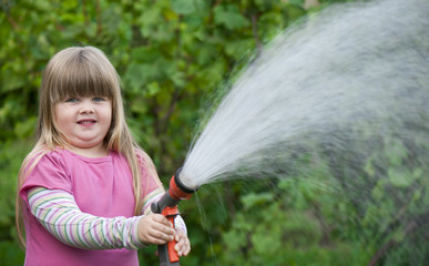 girl watering the grass