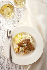 close up beef roast and risotto in white dish
