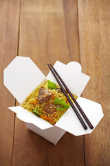 close up chinese noodle and fish fried in paper box