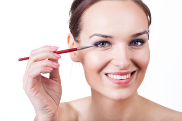 Woman applying eyeliner with brush