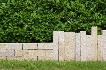Moderne Gartenmauer aus Granitsäulen und Hecke