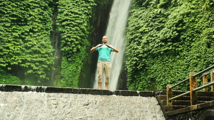 Man doing breathing exercise by waterfall, Bali, Indonesia