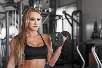 Blonde bodybuilder workout with dumbbell
