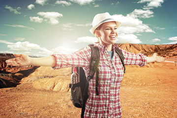 Happy smiling female traveler with backpack in the desert.