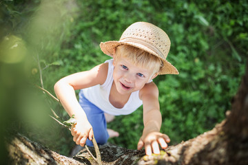 beautiful child with a straw hat climbs in a tree