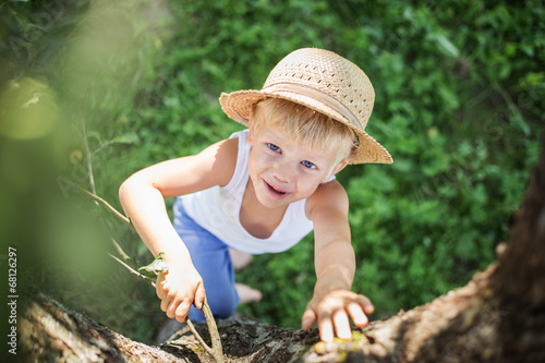 beautiful child with a straw hat climbs in a tree - 68126297