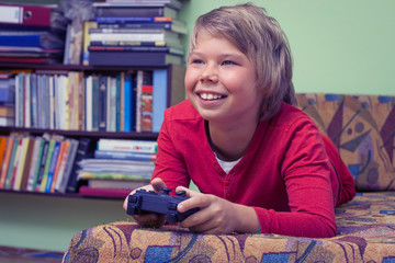 Boy teenager playing a video game console.