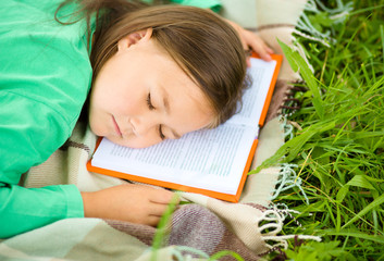 Girl is sleeping on her book outdoors