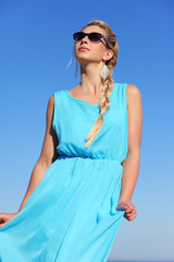 girl in a blue dress and sunglasses on background of sky