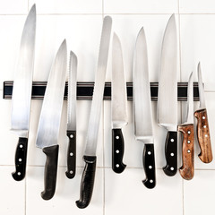Set of knives on magnetic holder on white tiles