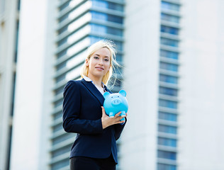 Happy business woman holding piggy bank