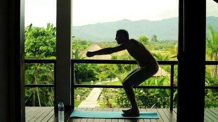 Silhouette of man doing squats, exercising on terrace