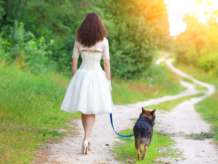 Young bride walking with dog on the rural road