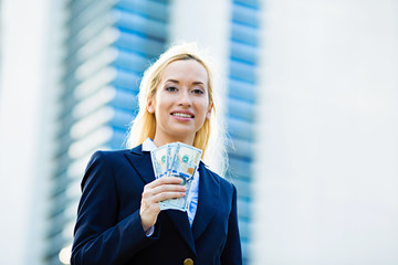 Happy woman holding dollar bills, corporate office background