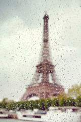 View on the Eiffel Tower through the window with rain drops.