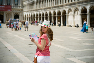 Young girl with map at San Marco square in Venice