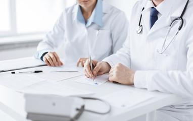 doctor and nurse writing prescription paper