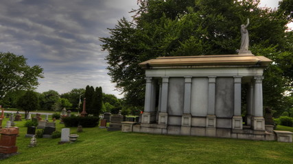 Timelapse view in a cemetery with mausoleum in foreground