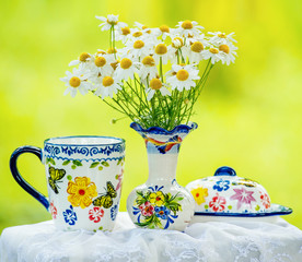 Daisies bouquet in vase and colorful crockery