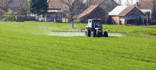 Farmer spraying wheat field at spring season