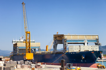 loading cargo ship docked in industrial harbor