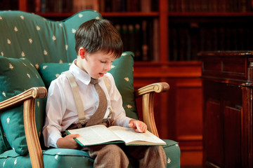 Cute little boy reading book on armchair