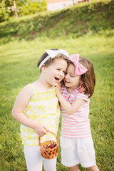 Two little sisters hugging and laughing outdoors
