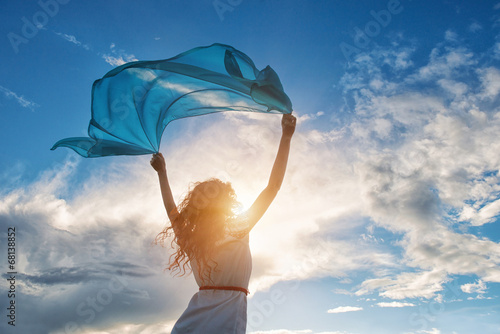 Beautiful young woman holding blue scarf on the wind - 68138852