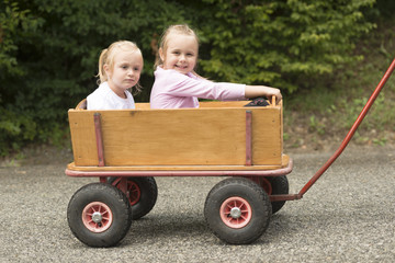 Two Cute little girls in a cart