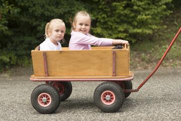 Two Cute little girls in a cart