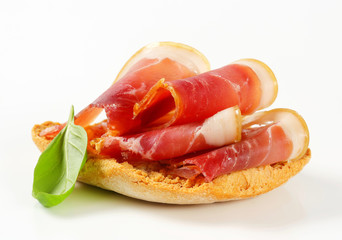 Slices of prosciutto on crispy bread
