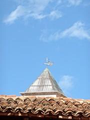 campanile dietro ad un tetto di tegole