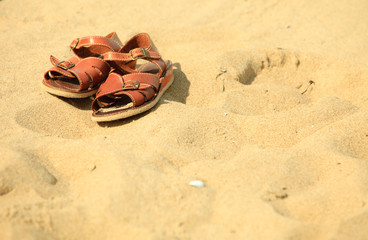 Shoes. Brown leather sandals on a sandy beach. Summertime.