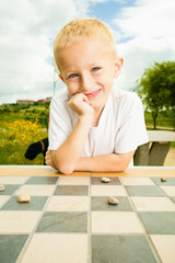 Child playing draughts or checkers board game outdoor