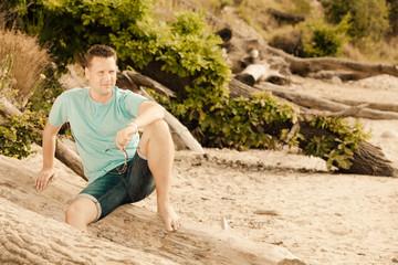 Fashion portrait handsome man sitting on tree