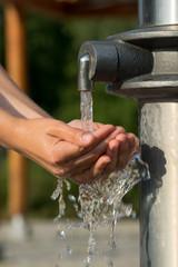 Hände fangen kühles und klares Wasser aus einem Brunnen auf