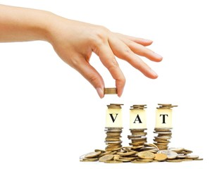 hand giving coins to piles of coins with the word VAT