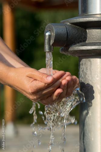 canvas print picture Hände fangen kühles und klares Wasser aus einem Brunnen auf