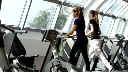 gym shot - people running on machines, treadmill; young women