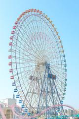 A big ferris wheel under bright blue sky.