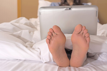 woman using laptop on the bed