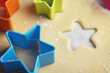 Close up star shaped cookie cutters in dough