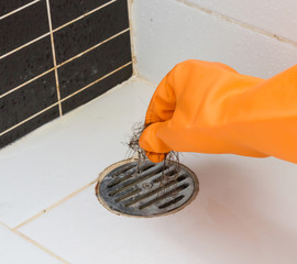 Cleaning bathroom  hair clogged with orange gloves.