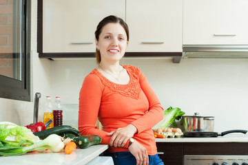 woman with fresh vegetables in  kitchen